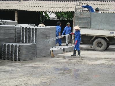 Một cơ sở sản xuất amiăng đang phun nước lên các tấm ngói nhằm hạn chế bụi